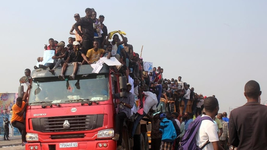 Supporters of Congo opposition leader Etienne Tshisekedi, on board of a truck as they await his arrival near the airport in Kinshasa, Congo, Wednesday, July 27, 2016. The head of the main opposition party in Congo has returned home after two years away for medical reasons and as tensions grow ahead of November elections. Hundreds of supporters greeted Etienne Tshisekedi at the Kinshasa airport Wednesday. (AP Photo/John Bompengo)