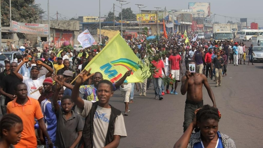 Supporters of Congo opposition leader Etienne Tshisekedi, near the airport in an main street as they await his in Kinshasa, Congo, Wednesday, July 27, 2016.The leader of Congo's main opposition party returned to the country Wednesday after two years away for medical reasons and as tensions grow ahead of November presidential elections.(AP Photo/John Bompengo)