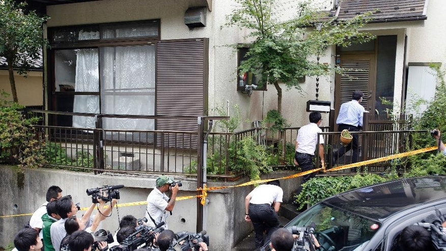 Police officers enter into the house of Satoshi Uematsu, the suspect in a mass stabbing attack, in Sagamihara, outside of Tokyo, Wednesday, July 27, 2016. The suspect was being transferred Wednesday from a local police station to the prosecutor's office in Yokohama. (AP Photo/Shizuo Kambayashi)