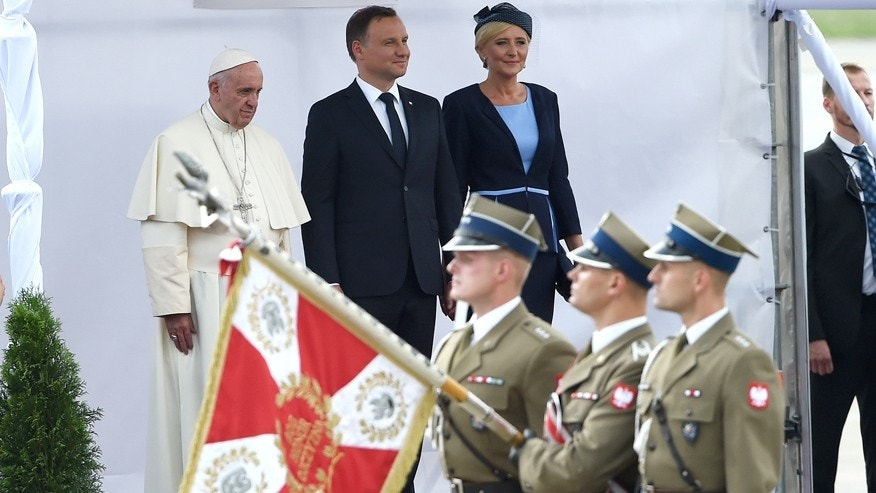 July 27, 2016: Pope Francis, with Polish President Andrzej Duda, center, and First Lady Agata Kornhauser-Duda watch attends the welcome ceremony upon his arrival at the military airport in Krakow, Poland.