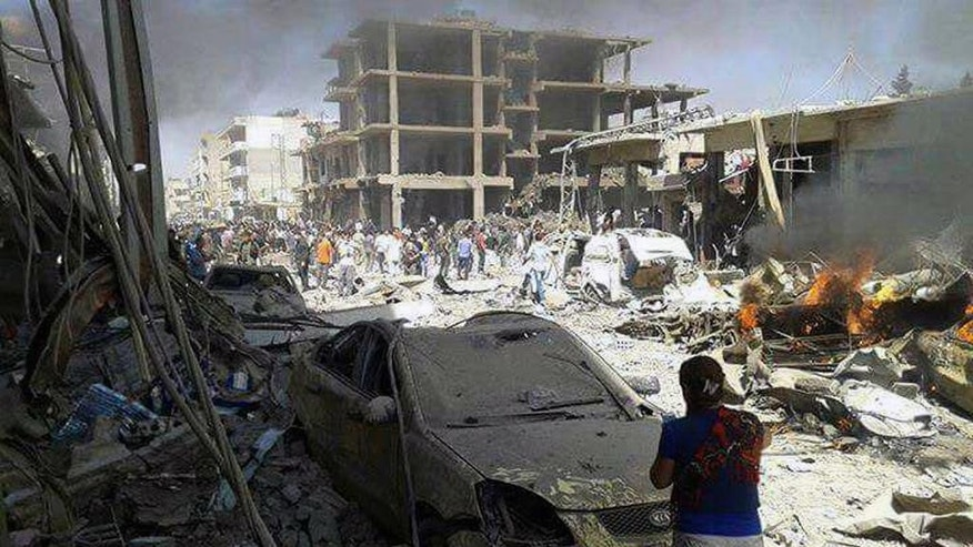 In this photo released by the Syrian official news agency SANA, Syrians inspect damages after deadly twin bombings struck the town of Qamishli, Syria, Wednesday, July 27, 2016. The bombings struck a crowd in the predominantly Kurdish town in northern Syria on Wednesday, killing and wounding dozens of people, Syria's state-run news agency and Kurdish media reported. State-run TV said a truck loaded with large quantities of explosives blew up on the western edge of the town of Qamishli, followed by an explosives-packed motorcycle few minutes later in the same area. (SANA via AP)