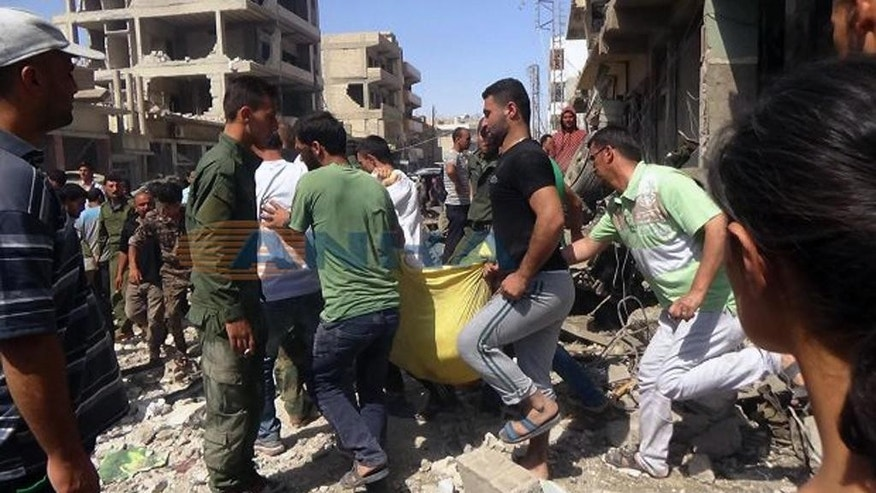 In this photo released by the news outlet ANHA via the Syrian official news agency SANA, Syrians carry a victim after twin bombings struck Kurdish town of Qamishli, Syria, Wednesday, July 27, 2016. Bombings struck a crowd in a predominantly Kurdish town in northern Syria on Wednesday, killing 44 people and wounding dozens more, Syria's state-run news agency and Kurdish media reported. (SANA via AP)