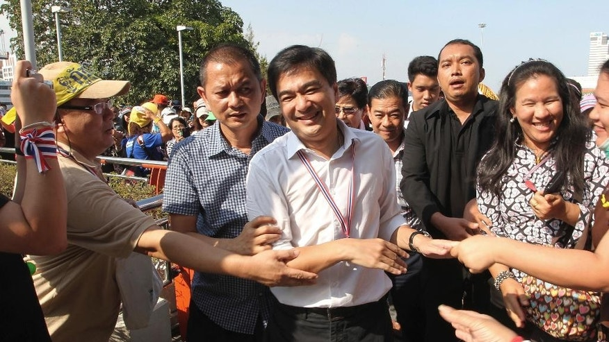 FILE- In this Monday, Jan. 13, 2014, file photo, former Thailand Prime Minister Abhisit Vejjajiva, center, is greeted by supporters as he appears at an overfly near Victory Monument where anti-government protesters gather for a rally in Bangkok, Thailand. Former Prime Minister Abhisit Vejjaviva on Wednesday, July 27, 2016, joined a growing chorus of voices opposed to a new constitution proposed by the military government. (AP Photo/Apichart Weerawong, File)
