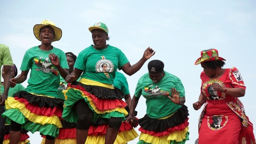"Members of Mbare Chimurenga sing and dance before the arrival of Zimbabwean President Robert Mugabe, at the Zanu PF party headquarters, in Harare, Wednesday, July, 27, 2016. Zimbabwe's 92-year-old president on Wednesday said the longtime loyalists who turned against him last week should face ""severe"" punishment, and he vowed to stay in power for ""a long time."" (AP Photo/Tsvangirayi Mukwazhi)"