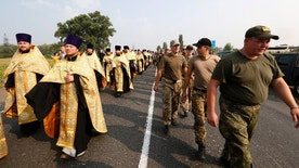 In this photo taken on Monday, July 25, 2016, Ukrainian clergymen and national guards, right, walk to the city Boryspil, Ukraine. Ukraine's interior minister on Tuesday, July 26 bent to the pressure of nationalists and ordered police to bar a major religious procession from entering the capital, Kiev, after police found ammunition planted along the planned route. Ukrainian nationalists have previously threatened to attack the procession if it enters Kiev. (AP Photo/Sergei Chuzavkov)