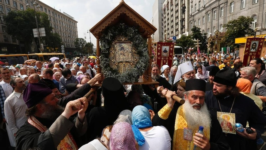 Orthodox believers and clergymen participate in a procession downtown Kiev, Ukraine, Wednesday, July 27, 2016. The processions are in observance of the holiday marking the adoption of Christianity by what is now Russia and Ukraine in the 10th century. They are to commemorate the day at the hillside monument in central Kiev to Saint Volodymyr, the prince who enacted the adoption of Christianity. (AP Photo/Sergei Chuzavkov)