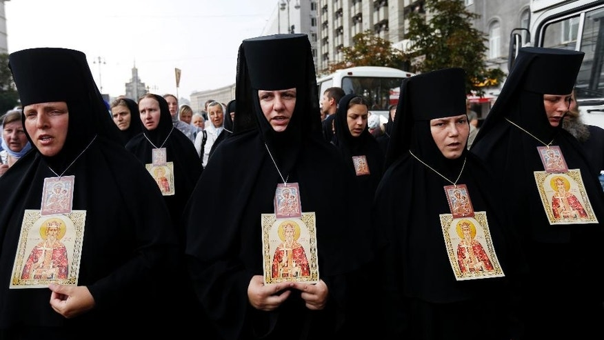 Orthodox nuns walk to prayer in downtown Kiev, Ukraine, Wednesday, July 27, 2016 in observance of the holiday marking the adoption of Christianity by what is now Russia and Ukraine in the 10th century. They are to commemorate the day at the hillside monument in central Kiev to Saint Volodymyr, the prince who enacted the adoption of Christianity. (AP Photo/Sergei Chuzavkov)