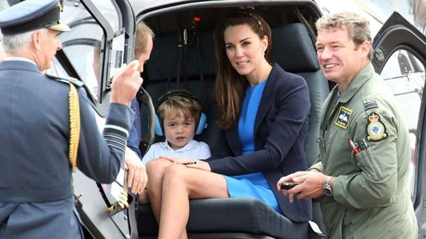 Prince George, center left, sits in a helicopter with his mother Kate, the Duchess of Cambridge, during a visit to the Royal International Air Tattoo at RAF Fairford