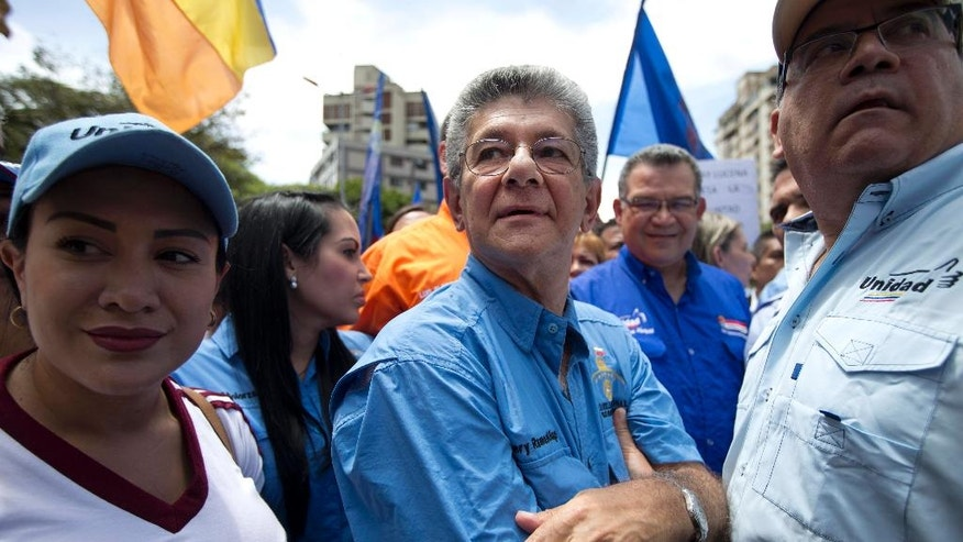 Venezuelan National Assembly President Henry Ramos Allup, center, takes part in a protest march in Caracas, Venezuela, Wednesday, July 27, 2016. Venezuela's opposition marched Wednesday to demand electoral officials go forth with the recall referendum process against Maduro. Venezuela's socialist government appears to be digging in its heels to stop the presidential recall vote. The elections board missed its own deadline to certify signatures on the petition demanding the start of a recall process. (AP Photo/Ariana Cubillos)
