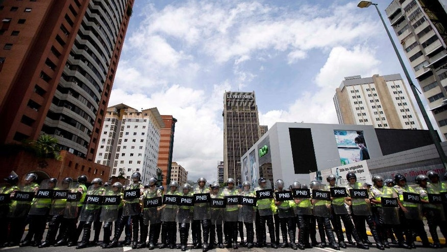 A cordon of Bolivarian National Police block an avenue to prevent opposition marchers from reaching the National Electoral Council building in Caracas, Venezuela, Wednesday, July 27, 2016. Venezuela's opposition marched Wednesday to demand electoral officials go forth with the recall referendum process against Maduro. Venezuela's socialist government appears to be digging in its heels to stop the presidential recall vote. The elections board missed its own deadline to certify signatures on the petition demanding the start of a recall process.(AP Photo/Ariana Cubillos)
