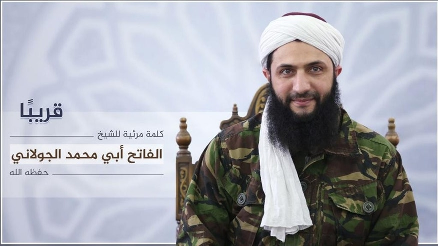 "Nusra Front leader Mohammed al-Golani undated photo released online on Thursday, July 28, 2016 to announce a video message that the militant group is changing name, and claims it will have no more ties with al-Qaida. In a video aired on the Syrian opposition station Orient TV and Al-Jazeera  al-Golani said the delinking from the terror network aimed to remove ""pretexts"" by the U.S. and Russia to strike other rebel groups while claiming they are targeting Nusra. Arabic reads, ""coming soon, a video by the conqueror, Mohammed al-Golani.""  (militant photo via AP)"
