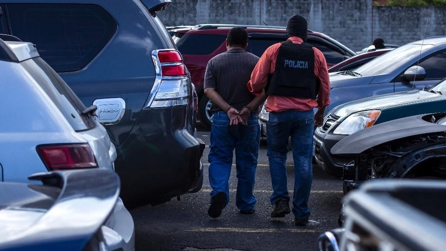 A suspected Mara Salvatrucha, or MS, gang member is taken away by a police officer after he was arrested and shown to the press in San Salvador, El Salvador, Thursday, July 28, 2016. Authorities in El Salvador are claiming a strong blow against the leadership and financing of the MS, one of the country's principal street gangs. A police spokesman says they seized weapons, cash and vehicles during raids at homes, restaurants, bars, motels, mechanic garages and a car lot. They froze 30 bank accounts allegedly tied to the gang and arrested 77 people, including the man in charge of the gang's finances, who is also an evangelical preacher. (AP Photo/Salvador Melendez)