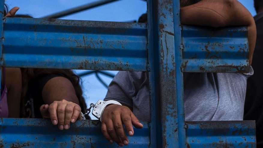 Suspected Mara Salvatrucha, or MS,  gang members sit in the back of a truck after they were arrested and shown to the press in San Salvador, El Salvador, Thursday, July 28, 2016. Authorities in El Salvador are claiming a strong blow against the leadership and financing of the MS, one of the country's principal street gangs. A police spokesman says they seized weapons, cash and vehicles during raids at homes, restaurants, bars, motels, mechanic garages and a car lot. They froze 30 bank accounts allegedly tied to the gang and arrested 77 people, including the man in charge of the gang's finances, who is also an evangelical preacher. (AP Photo/Salvador Melendez)