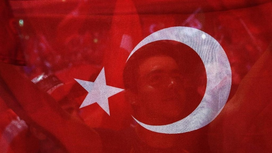 A man holds a Turkish flag during an anti coup rally at Taksim square in Istanbul, Tuesday, July 26, 2016.  Turkey's polarized factions should learn from their mistakes and overcome their antagonism, the main opposition leader Kemal Kilicdaroglu said during an interview with The Associated Press. (AP Photo/Petros Karadjias)