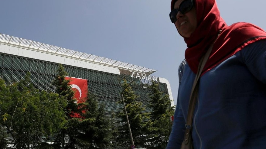 "A woman walks past the headquarters of 'Zaman' newspaper, after being closed by the government in Istanbul, Thursday, July 28, 2016. The European Union has called the crackdown on media in Turkey ""worrying"" and warned Ankara to respect fundamental freedoms. (AP Photo/Petros Karadjias)"