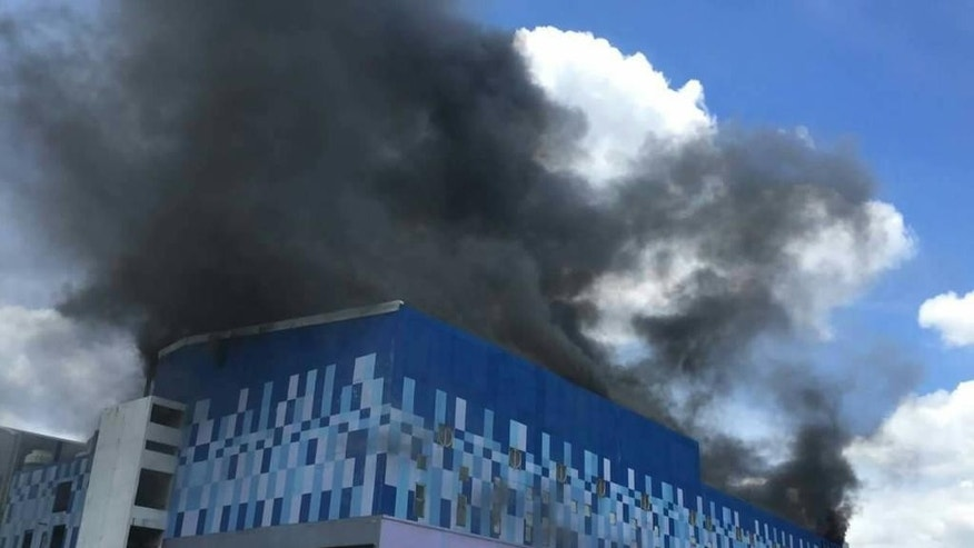 Smoke billows from the multi-screen Major Cineplex Pinklao in Bangkok, Thailand, Thursday, July 28, 2016. A large fire broke out at the popular movie theater complex Thursday morning, resulting two non-fatal injuries and the collapse of the building's roof. (Nikon Sethom via AP)