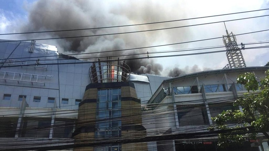 Smoke rises from the multi-screen Major Cineplex Pinklao in Bangkok, Thailand, Thursday, July 28, 2016. A large fire broke out at the popular movie theater complex Thursday morning, resulting two non-fatal injuries and the collapse of the building's roof. (Nikon Sethom via AP)