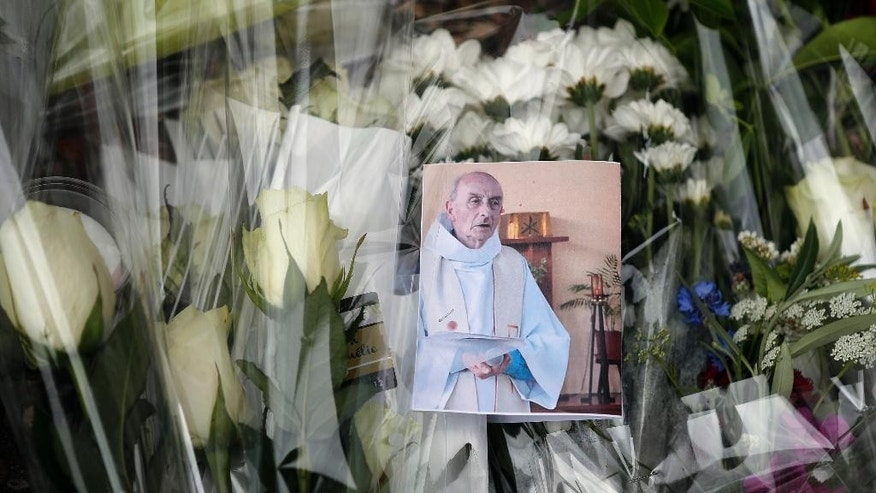 A picture of late Father Jacques Hamel is placed on flowers at the makeshift memorial in front of the city hall closed to the church where an hostage taking left a priest dead the day before in Saint-Etienne-du-Rouvray, Normandy, France, Wednesday, July 27, 2016. The Islamic State group crossed a new threshold Tuesday in its war against the West, as two of its followers targeted a church in Normandy, slitting the throat of an elderly priest celebrating Mass and using hostages as human shields before being shot by police. (AP Photo/Francois Mori)