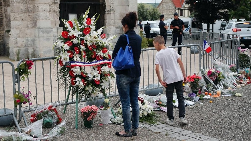 People gather to pay respect with flowers and candles next to the church where an hostage taking left a priest dead the day before in Saint-Etienne-du-Rouvray, Normandy, France, Wednesday, July 27, 2016. The Islamic State group crossed a new threshold Tuesday in its war against the West, as two of its followers targeted a church in Normandy, slitting the throat of an elderly priest celebrating Mass and using hostages as human shields before being shot by police. (AP Photo/Francois Mori)