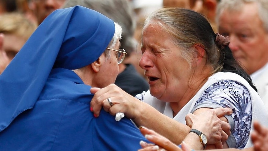 French nun greets a resident during a gathering in a town park for a solemn homage to the Rev. Jacques Hamel in Saint-Etienne-du-Rouvray, Normandy, France, Thursday, July 28, 2016. Saint-Etienne's mayor Hubert Wulfranc called for a solemn homage to the Rev. Jacques Hamel on Thursday, for a moment of silence followed by the French national anthem. (AP Photo/Francois Mori)
