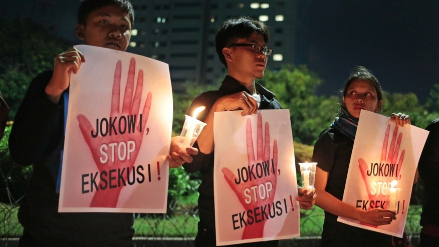 "Activists hold posters which read ""Jokowi, stop the executions!"" during a vigil outside the presidential palace in Jakart. ""Jokowi"" is the popular nickname of Indonesian President Joko Widodo."