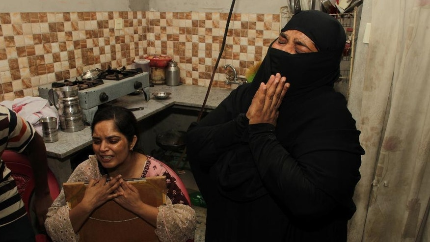 Sajida Bibi, right, sister of Zulfikar Ali, convicted of drug crimes, cries with her sister Humaira Bibi, in Lahore, Pakistan, Wednesday, July 27, 2016. The sister of a Pakistani convicted of drug crimes has appealed the Indonesian government to spare the life of her ailing brother who is expected to be executed by a firing squad along with 12 others in the next 48 hours. (AP Photo/K.M. Chaudary)