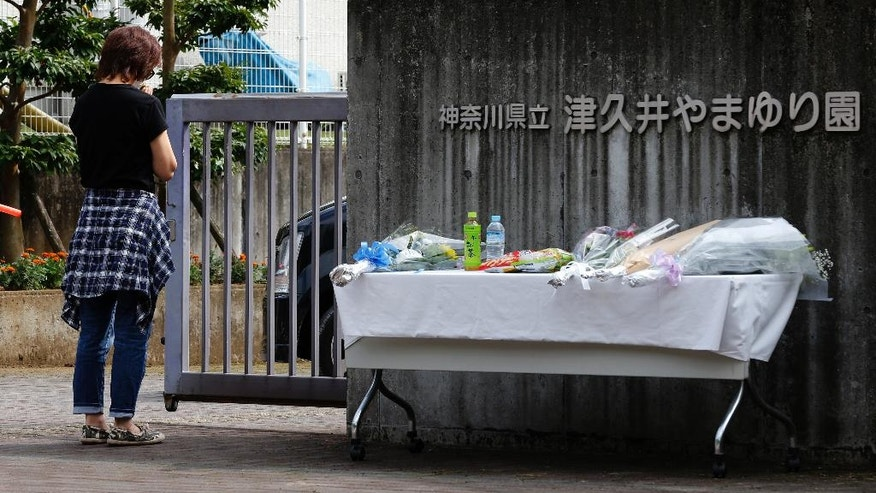 A woman prays in front of the Tsukui Yamayuri-en, a facility for the mentally disabled where a number of people were killed and dozens injured in a knife attack in Sagamihara, outside of Tokyo, Japan, Wednesday, July 27, 2016. Japanese police on Wednesday searched the home of the suspect in the mass stabbing spree. (AP Photo/Shizuo Kambayashi)