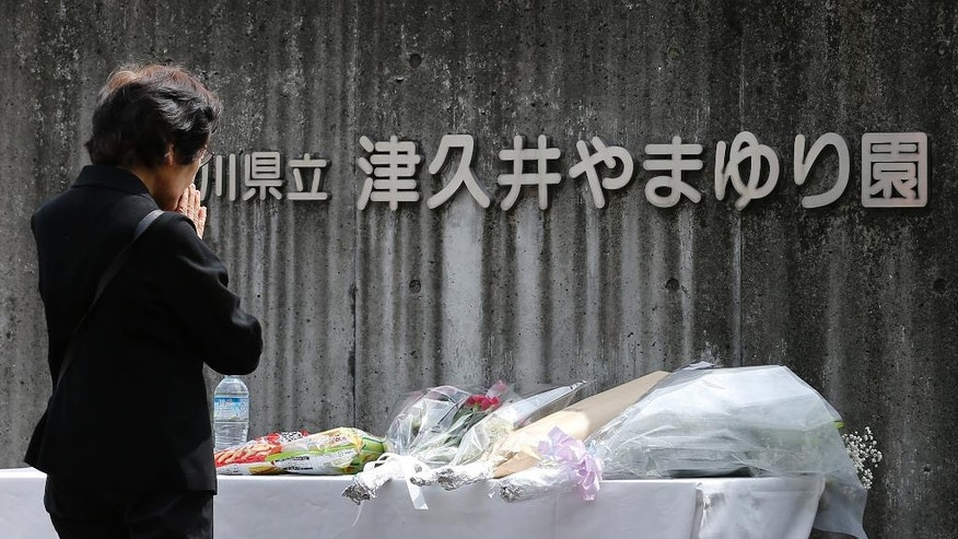 A woman prays in front of the Tsukui Yamayuri-en, a facility for the mentally disabled where a number of people were killed and dozens injured in a knife attack, in Sagamihara, outside of Tokyo, Wednesday, July 27, 2016. Japanese police on Wednesday searched the home of the suspect in the mass stabbing spree. (AP Photo/Shizuo Kambayashi)
