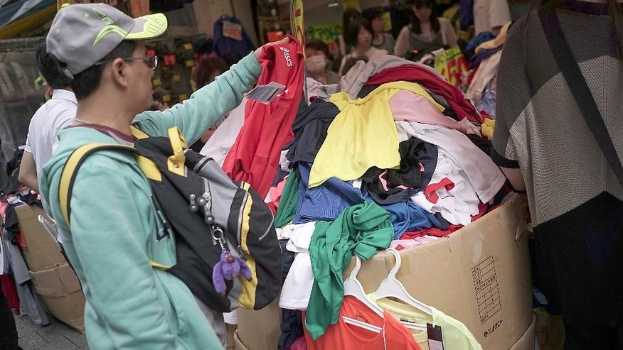 In this July 23, 2016, photo, a man looks at clothing on sale at a shop in Tokyo. Japan's central bank has opted for a modest expansion of its lavish monetary stimulus to help perk up sluggish growth and combat deflation. (AP Photo/Eugene Hoshiko)