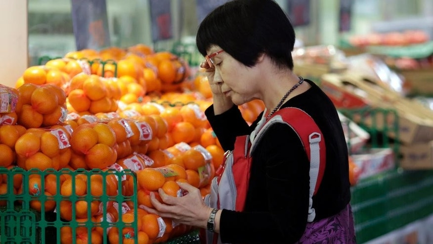 FILE - In this Nov. 17, 2015 file photo, a woman takes a look at orange on sale at a shop in Tokyo.  Japan reported further signs of weakness in its economy in June, with industrial output and consumer spending falling from the year before. The data released Friday, July 29, 2016,  were in line with expectations the central bank may follow the government's lead in opting for more stimulus at a policy meeting that ends Friday. (AP Photo/Eugene Hoshiko, File)