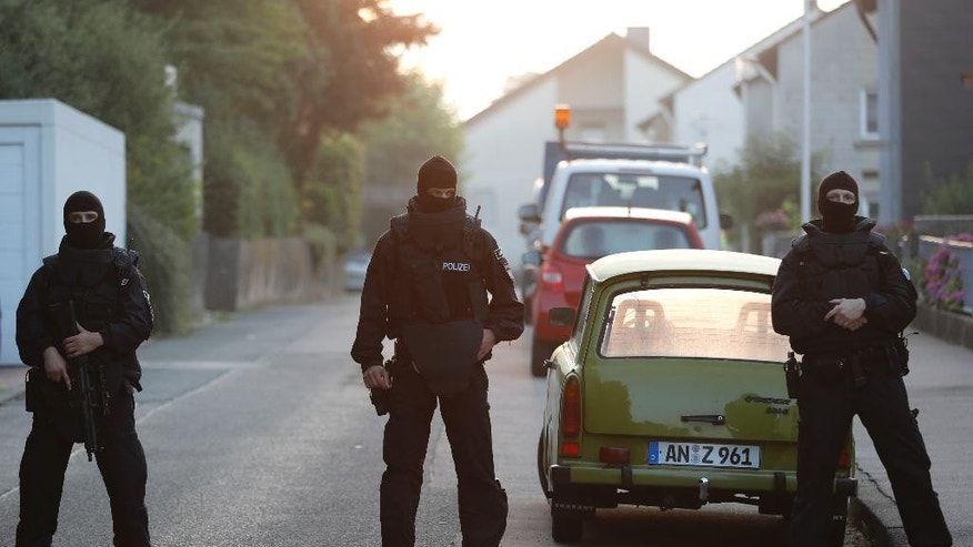 Special police officers secure a street near the house where a Syrian man lived before the explosion in Ansbach, southern Germany, Monday, July 25, 2016. The man who blew himself up and injured a dozen of people after being turned away from an open-air music festival was a Syrian who had been denied asylum, Bavaria's top security official said early Monday. (AP Photo/Matthias Schrader)