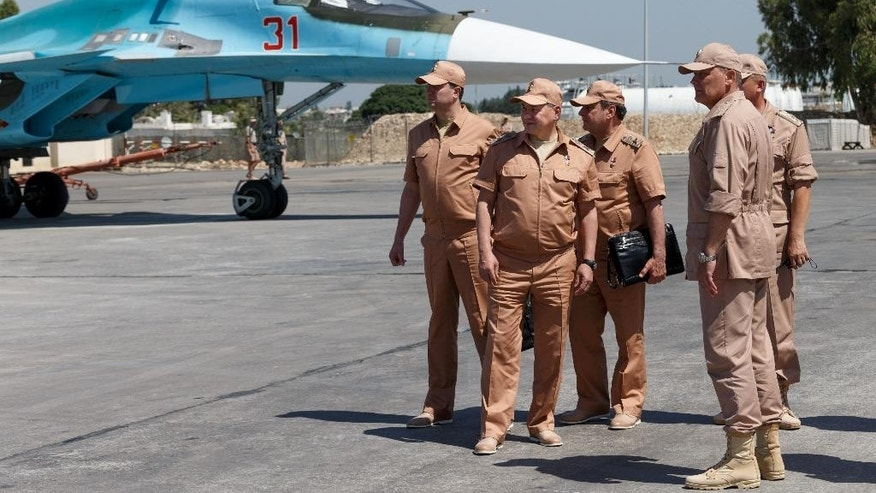 FILE - In this Saturday, June 18, 2016 file photo, Russian Defense Minister Sergei Shoigu, second left, visits the Hemeimeem air base in Syria. Shoigu said on Thursday, July 28, 2016 that Russia and the Syrian government will open humanitarian corridors and offer a way-out for Islamic State fighters wanting to lay down their arms. (Vadim Savitsky/Russian Defense Ministry Press Service Pool Photo via AP, file)