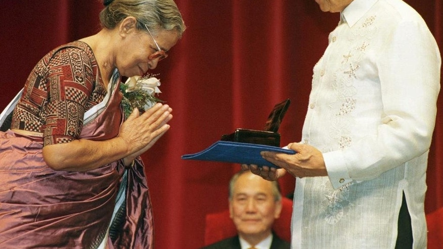 FILE- In this Aug. 31, 1997 file photo, Philippine President Fidel Ramos presents the 1997 Ramon Magsaysay Award for Journalism, Literature and Creative Communication Arts to Mahasweta Devi of India during the award ceremony in Manila. Devi, a well-known Indian writer and social activist, who used her writing to give voice to the oppressed poor tribal and forest dwellers died Thursday, July 28, 2016 at a Kolkata hospital. She was 90. (AP Photo/Victoria Calaguian, File)