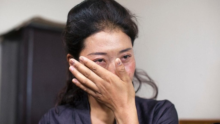 "In this Wednesday, July 27, 2016 photo, Nyima Lhamo, 26, wipes a tear as she talks about her uncle Tenzin Delek Rinpoche, a prominent Tibetan religious leader who died in prison last year, during an interview with the Associated Press in Dharmsala, India. She arrived in the northern hill town of Dharmsala via Nepal Sunday after two weeks on the road with the help of smugglers who she paid $9,700 for the trip, leaving her aging mother and a six-year-old daughter, whom she may never see again. ""It was necessary as the story of my uncle had to be told to the world. We don't trust what China is telling us and demand a thorough investigation into his death,"" she said, speaking through two translators. (AP Photo/Ashwini Bhatia)"