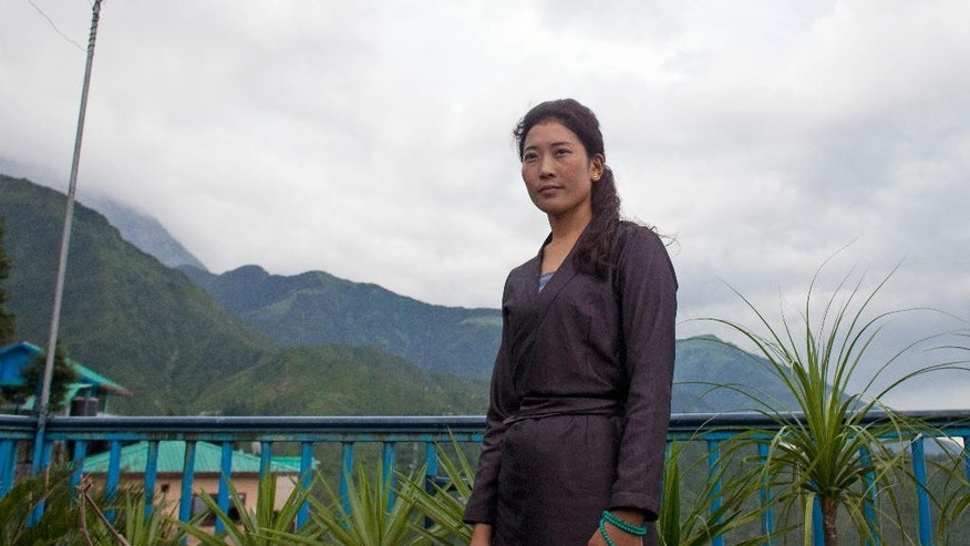In this Wednesday, July 27, 2016 photo, Nyima Lhamo, 26, poses for a photograph after an interview with the Associated Press in Dharmsala, India, where she narrated the story of her escape from Tibet. Lhamo, the niece of a prominent Tibetan religious leader, fled China and arrived in exile in northern India to reveal what her family says is the truth about his death. Her uncle Tenzin Delek Rinpoche died in prison on July 13, 2015, after attempts by several human rights groups to secure him medical parole failed. (AP Photo/Ashwini Bhatia)