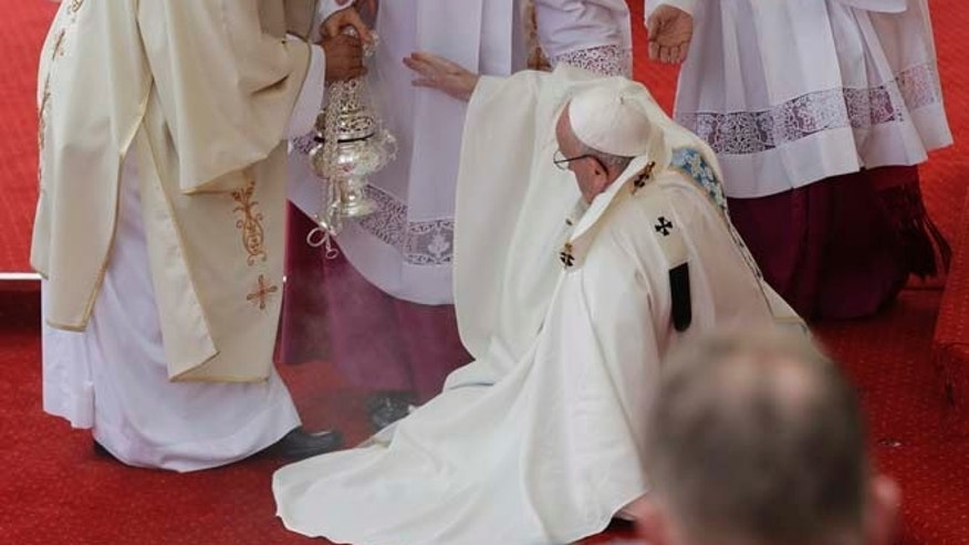 Pope Francis is helped by Vatican Master of Ceremonies, Mons. Guido Marini as he stumbles on the altar as he celebrates a mass in Czestochowa, Poland