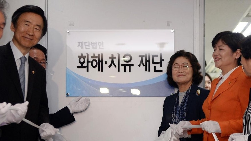 South Korean Foreign Minister Yun Byung-se, left, Kim Tae-hyun,  second right, head of a committee, and Kang Eun-hee, right, minister of Gender Equality and Family attend the office opening ceremony for a preparation committee for a fund aimed at compensating Korean victims of Japanese wartime military brothels, in Seoul Thursday, July 28, 2016. The sign reads Reconciliation and Healing Foundation. (Song Kyung-seok/Kyodo News via AP)