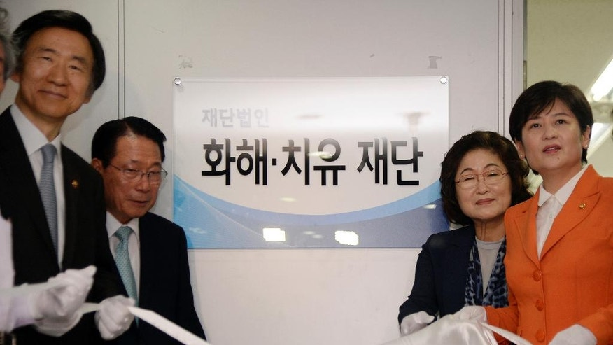 South Korean Foreign Minister Yun Byung-se, left, Kim Tae-hyun, second right, head of a preparation committee for a fund aimed at compensating Korean victims of Japanese wartime military brothels, and Kang Eun-hee, right, minister of Gender Equality and Family attend the office opening ceremony of the committee in Seoul, South Korea Thursday, July 28, 2016. The sign reads Reconciliation and Healing Foundation.  (Song Kyung-seok/Pool Photo via AP)