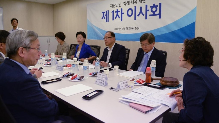 """Kim Tae-hyun, right, head of a preparation committee for a fund aimed at compensating Korean victims of Japanese wartime military brothels, attends with other members at their first board meeting in Seoul, South Korea Thursday, July 28, 2016. The sign reads """"the first council meeting."""" (Song Kyung-seok/Pool Photo via AP)"""