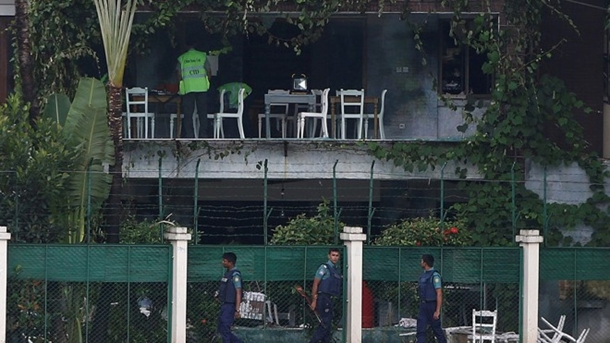 July 3: Policemen patrol outside the Holey Artisan Bakery and the O'Kitchen Restaurant as others inspect the site after gunmen attacked, in Dhaka, Bangladesh