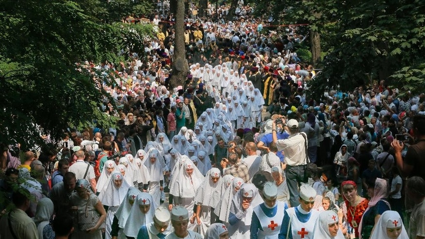 Orthodox believers and clergymen march to prayer in downtown Kiev, Ukraine, Wednesday, July 27, 2016 in observance of the holiday marking the adoption of Christianity by what is now Russia and Ukraine in the 10th century. They are to commemorate the day at the hillside monument in central Kiev to Saint Volodymyr, the prince who enacted the adoption of Christianity. (AP Photo/Efrem Lukatsky)