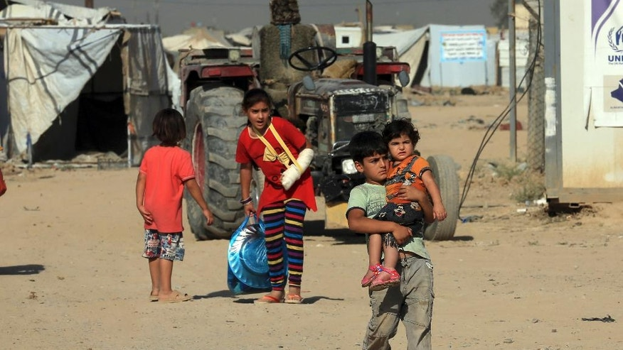Internally displaced children prepare to return home to Anbar province, at a camp in southern Baghdad, Iraq, Thursday, July 28, 2016. More than 120 families have started returning to their homes in Iraq's Anbar province after the region was liberated from the control of Islamic State group extremists. (AP Photo/Khalid Mohammed)