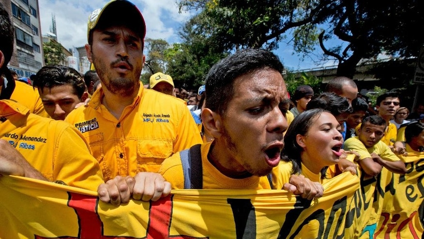 "Opposition members shout ""Recall now"" during a protest march against Venezuela's President Nicolas Maduro in Caracas, Venezuela, Wednesday, July 27, 2016. Venezuela's opposition marched Wednesday to demand electoral officials go forth with the recall referendum process against Maduro. Venezuela's socialist government appears to be digging in its heels to stop the presidential recall vote. The elections board missed its own deadline to certify signatures on the petition demanding the start of a recall process. (AP Photo/Fernando Llano)"