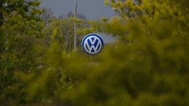 FILE - In this April 28, 2016 file picture  Volkswagen logo at a factory entrance stands behind green bushes during the company's annual press conference in Wolfsburg, Germany. Volkswagen says Wednesday July 27, 2016  its global sales rose 5.1 percent in June compared with a year earlier, fueled by gains in China and Europe and bolstering its performance over the year's first half. Deliveries in the U.S. were down significantly.   (AP Photo/Markus Schreiber,file)