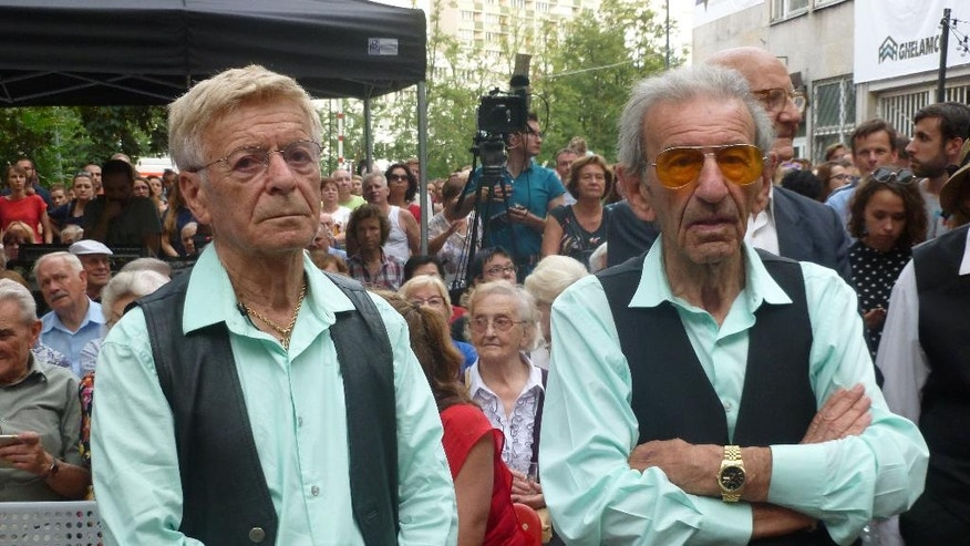 Holocaust survivors Reuwen 'Ruby' Sosnowicz, left, and Saul Dreier, members of the Holocaust Survivor Band, wait to go on stage for a performance in the former Warsaw Ghetto in Warsaw, Poland, on Tuesday July 26, 2016. Two Holocaust survivors took to a stage at the site of the former Warsaw Ghetto this week to perform lively prewar tunes, with a 91-year-old on drums and an 88-year-old on accordion, keyboard and vocals. Among the hundreds in the audience were several Polish Christians who saved Jews during the Holocaust, part of a complex relationship between Jews and Christians in Poland that Pope Francis will encounter during a somber visit to Auschwitz on Friday.   (AP Photo/Vanessa Gera)