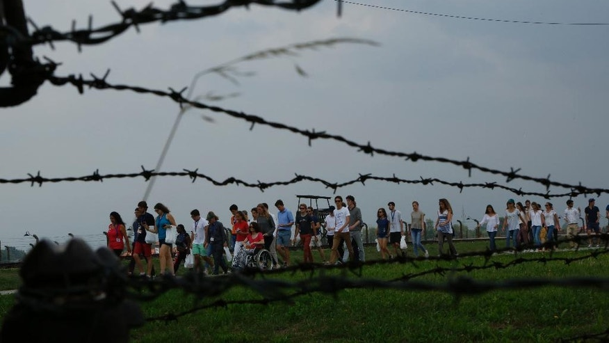 FILE- In this Monday, July 25, 2016 file photo, pilgrims walk on a path behind a wire fence in the former German Nazi Auschwitz-Birkenau death camp, in Oswiecim, Poland, to pay respect and pray. Thousands of catholic pilgrims begun pouring in Poland ahead a 5 day Pope Francis visit to this country. With his visit to Auschwitz, Francis will become the third pontiff to visit the site after predecessors John Paul II, a Pole, and Benedict XVI, a German. There he will pray at an execution wall and in the cell of St. Maximilian Kolbe, a Franciscan friar who volunteered to die at Auschwitz to save the life of a family father. (AP Photo/Amel Emric, File)