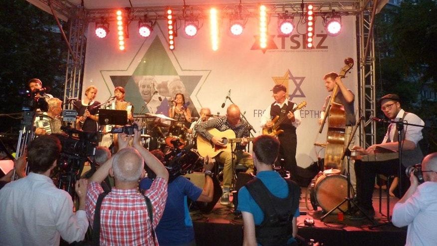 The Holocaust Survivor Band, made up of two Holocaust survivors who live in Florida, perform with Polish musicians in the area of the former Warsaw Ghetto in Warsaw, Poland, on Tuesday July 26, 2016. Two Holocaust survivors took to a stage at the site of the former Warsaw Ghetto this week to perform lively prewar tunes, with a 91-year-old on drums and an 88-year-old on accordion, keyboard and vocals. Among the hundreds in the audience were several Polish Christians who saved Jews during the Holocaust, part of a complex relationship between Jews and Christians in Poland that Pope Francis will encounter during a somber visit to Auschwitz on Friday. (AP Photo/Vanessa Gera)
