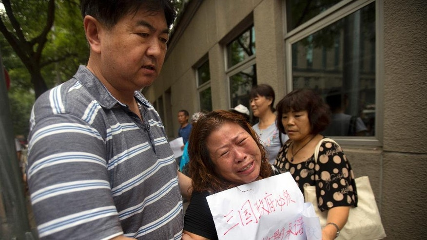 "A plainclothes official, left, escorts a woman holding a sign protesting the handling of the search for Malaysia Airlines Flight 370 outside Ministry of Foreign Affairs in Beijing, China, Friday, July 29, 2016. Several dozen relatives of passengers gathered at the ministry on Friday to hand over a letter of protest amid the recent announcement that the meticulous ocean search operations for the missing flight would soon be suspended. The sign reads ""The three countries' governments [involved in the search] must implement their promises to the world."" (AP Photo/Mark Schiefelbein)"