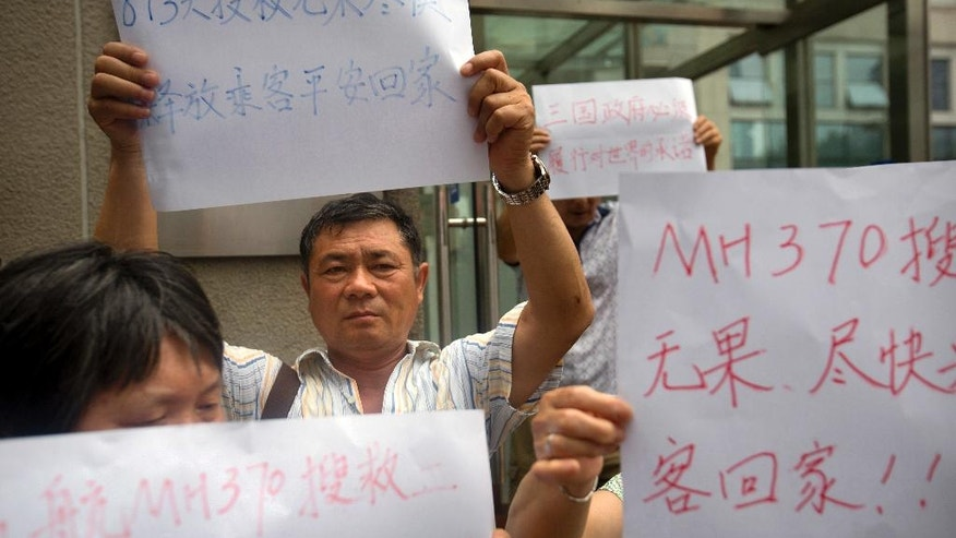 People hold signs protesting the handling of the search for Malaysia Airlines Flight 370 outside China's Ministry of Foreign Affairs in Beijing, China, Friday, July 29, 2016. Several dozen relatives of passengers gathered at the ministry on Friday to hand over a letter of protest amid the recent announcement that the meticulous ocean search operations for the missing flight would soon be suspended. (AP Photo/Mark Schiefelbein)'