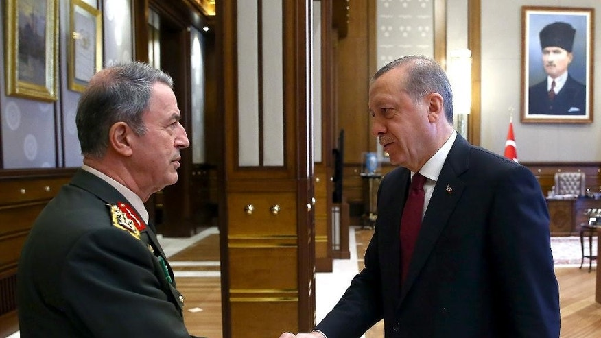 Turkey President Recep Tayyip Erdogan, right, shakes hands with the Chief of general staff General Hulusi Akar during a meeting with the top-level military meeting at the Presidential palace in Ankara, Turkey, on Friday, July 29, 2016. Erdogan met with Hulusi Akar, the four-star general who retained his position as chief of staff following a Supreme Military Council meeting, as well as other top military brass of the Turkish armed forces. (Kayhan Ozer/Presidential Press Service, Pool Photo via AP)